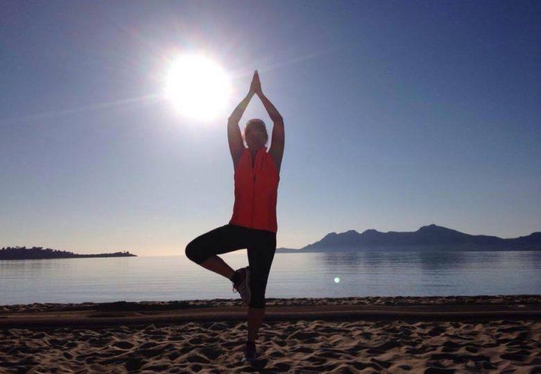 Yogaposition trädet på en strand med solen i bakgrunden